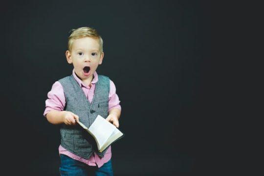 本を読み驚く少年